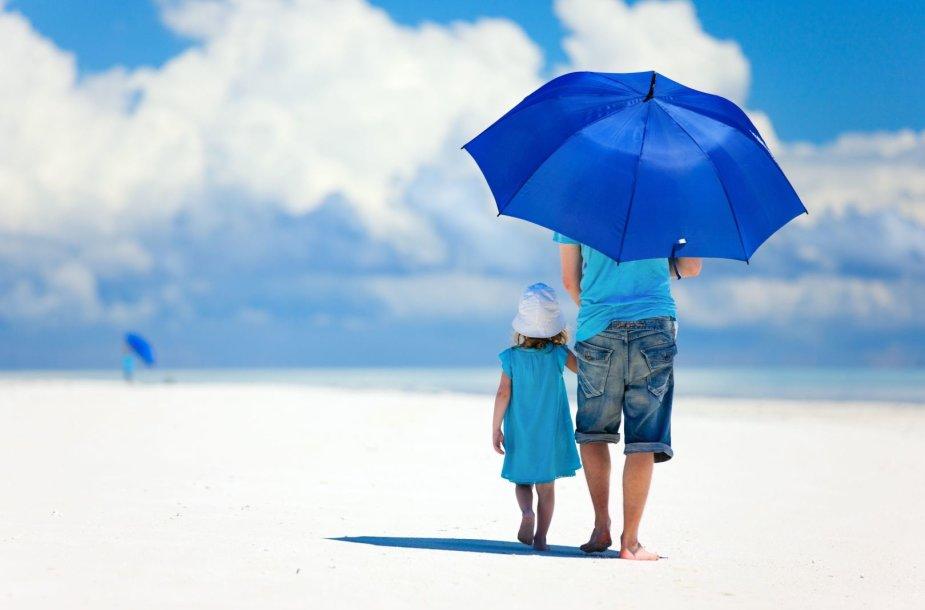 Tėtis vaikšto pajūriu su sūneliu