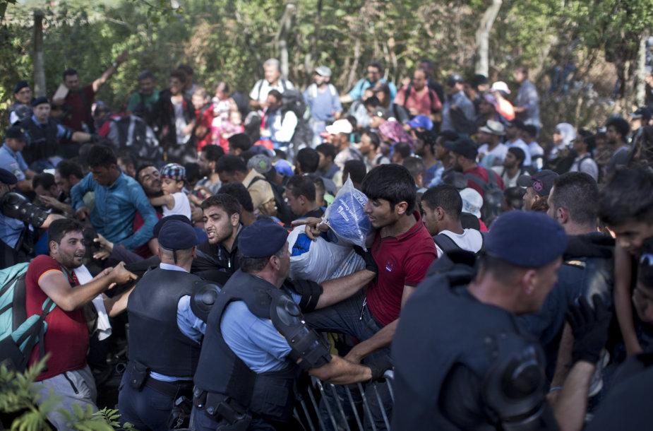 Migrantai Tovarnike braunasi pro pareigūnų užtvarą.
