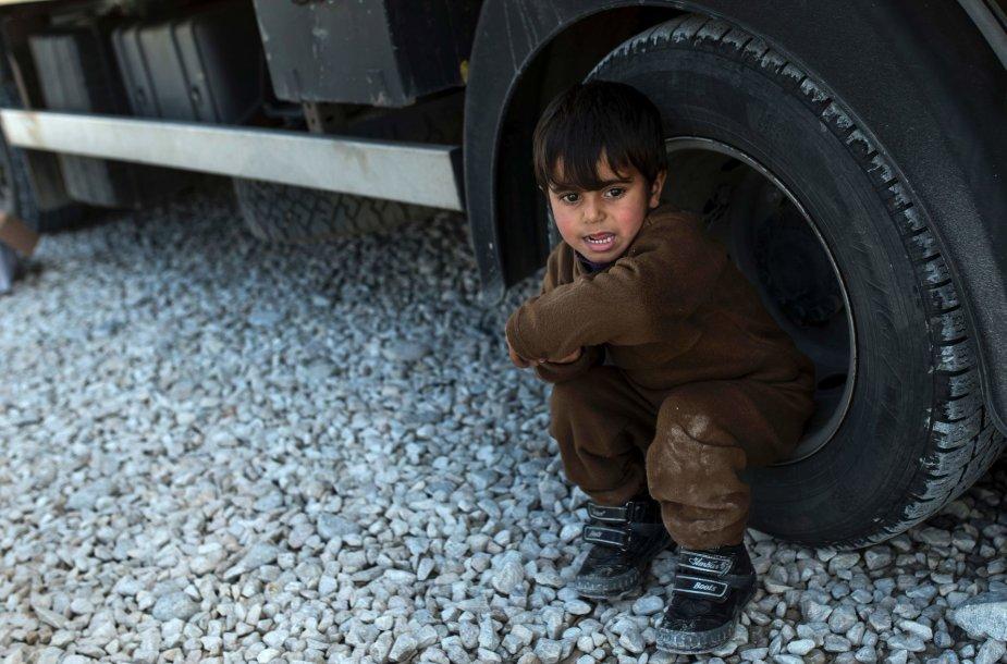 Migrantas vaikas prie sunkvežimio