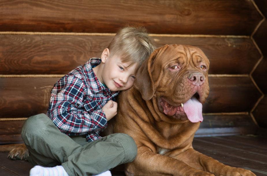 Vaikas su dideliu šunimi.