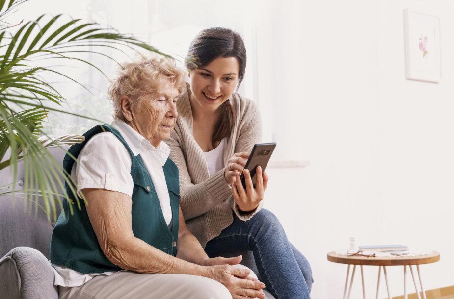 Vyresnė moteris naudojasi mobiliuoju telefonu