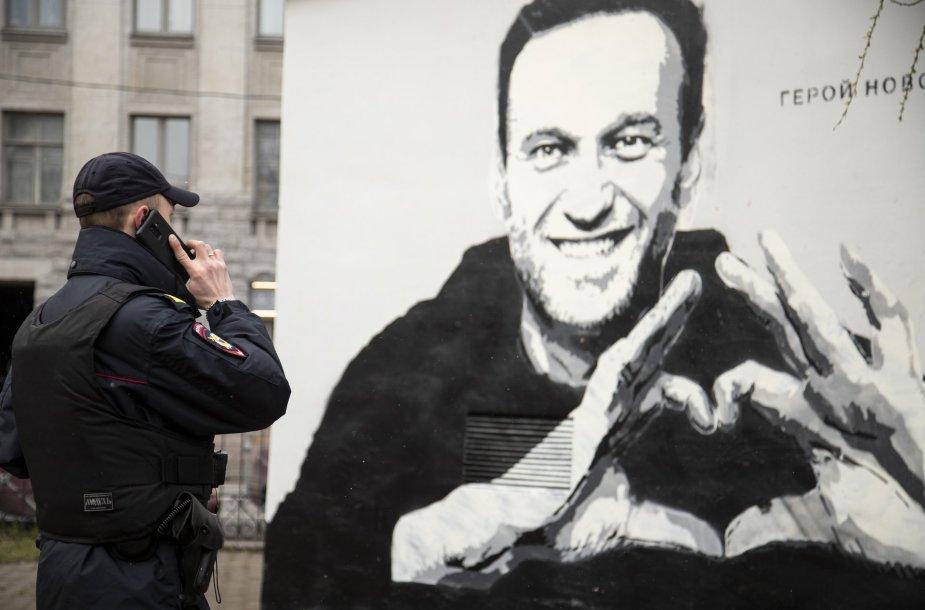 Pareigūnas prie Aleksejaus Navalno atvaizdo Sankt Peterburgas
