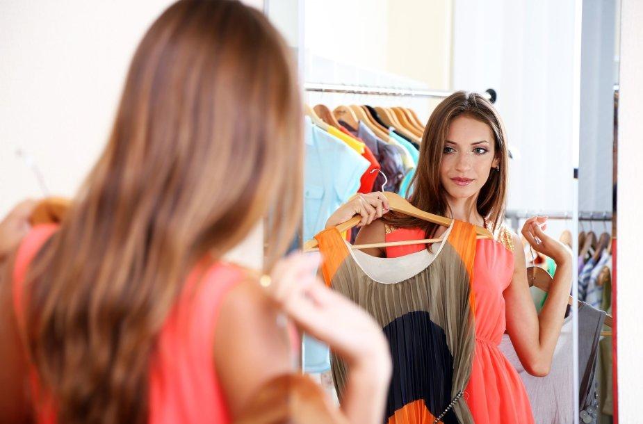 Mergina matavimosi kabinoje matuojasi suknelę
