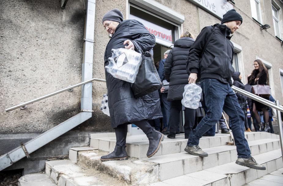 """Žmonės perka dezinfekcinį skystį """"Vilniaus degtinės"""" parduotuvėje"""