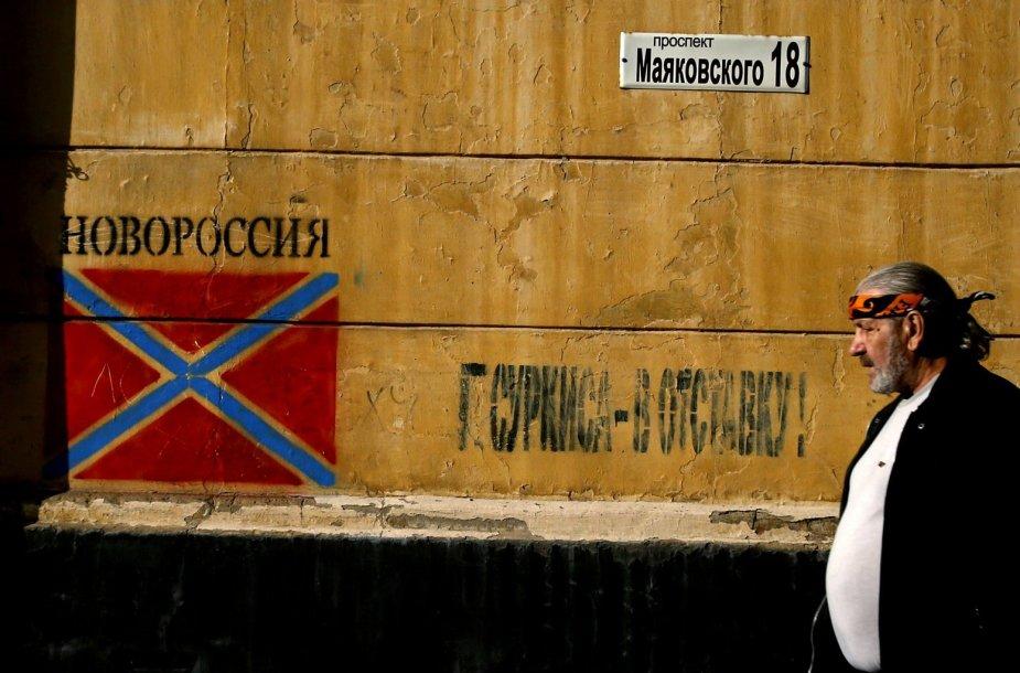 """Vyras eina pro grafitį su apsišaukeliškos """"Novorosijos"""" vėliava Donecke"""