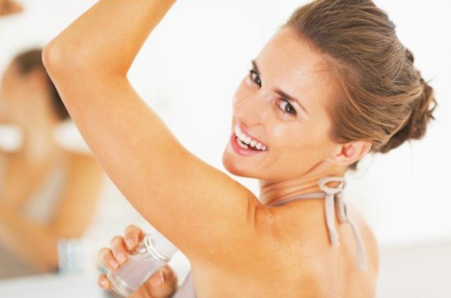 Moteris naudoja dezodorantą