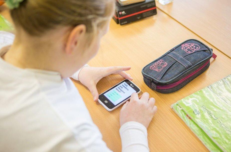 Mokiniai atsakinėja į klausimus išmaniaisiais telefonais