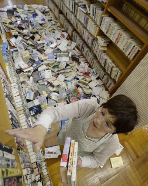 Po žemės drebėjimo Japonijoje bibliotekos darbuotoja deda knygas atgal į lentynas